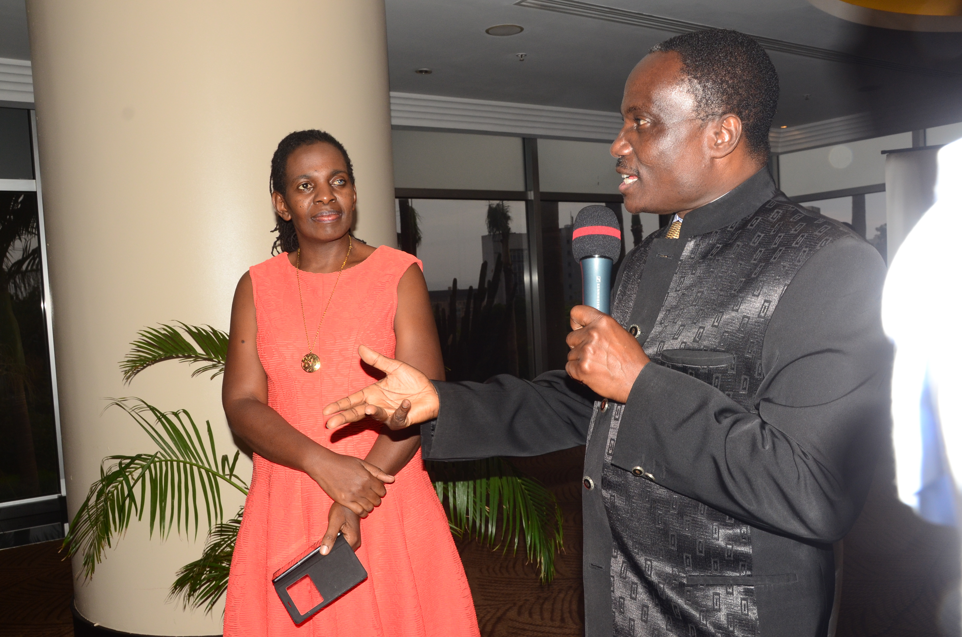 Mr Zacch Akinyemi (right) addressing guests at his farewell party while Dr Dorothy Balaba looks on